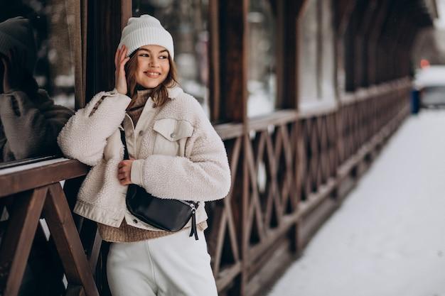 Giovane donna in abito invernale fuori strada