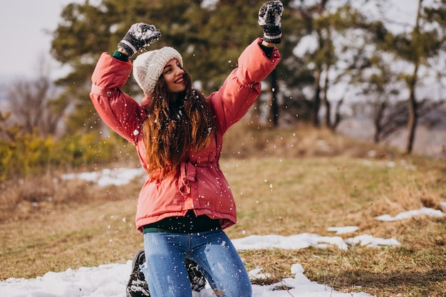 Young woman in winter park happy