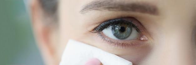 젊은 여자는 냅킨 클로즈업 청소로 얼굴을 닦습니다.