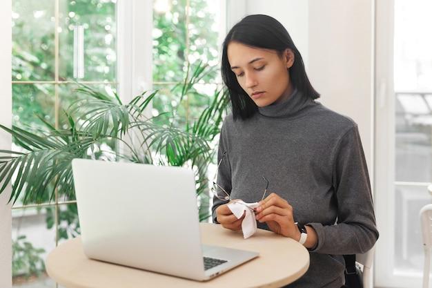 Молодая женщина вытирает очки во время работы за ноутбуком