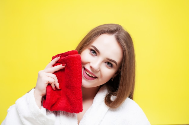 Молодая женщина вытирает лицо мягким полотенцем