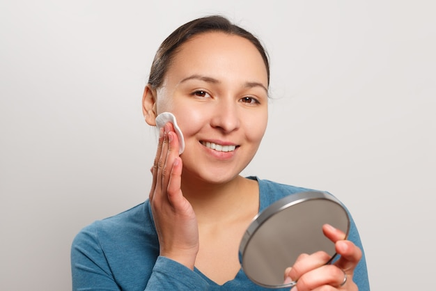 Young woman wipes her face with a cotton pad with lotion, looking at the mirror and smiling.