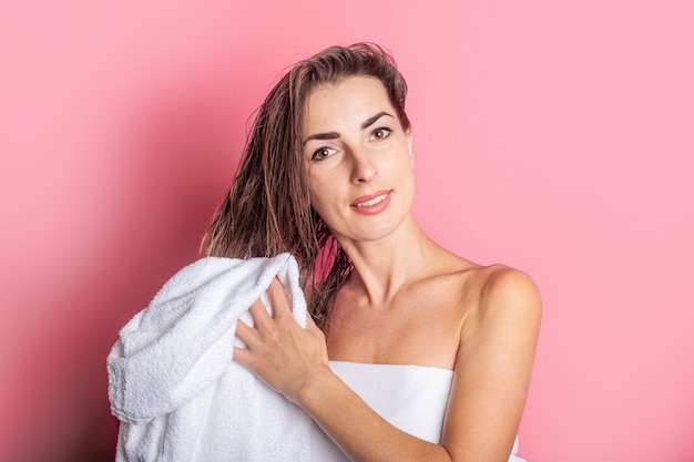 Young woman wipes her wet hair with a towel on a pink background.