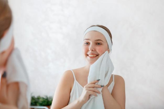 젊은 여성은 샤워 후 흰 수건으로 얼굴을 닦습니다. 아침에 화장실에서 셀프 케어. 행복한 미소 짓는 10대 소녀는 아침 일상적인 위생을 합니다. 거울에 초상화 반사입니다.
