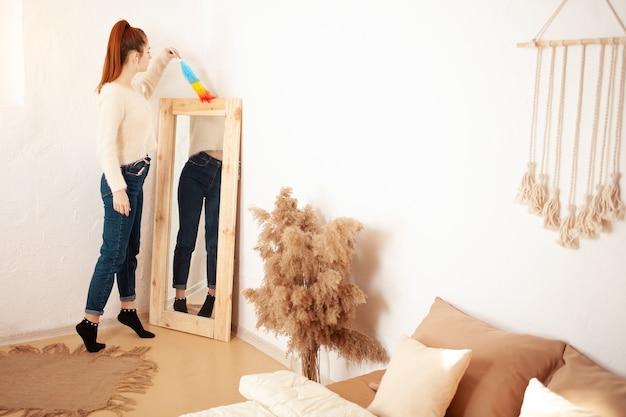 若い女性がふわふわのブラシで家の掃除をしている鏡からほこりを拭き取ります