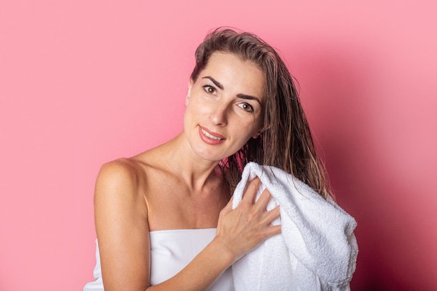 Young woman wipes wet hair with a towel on pink background.