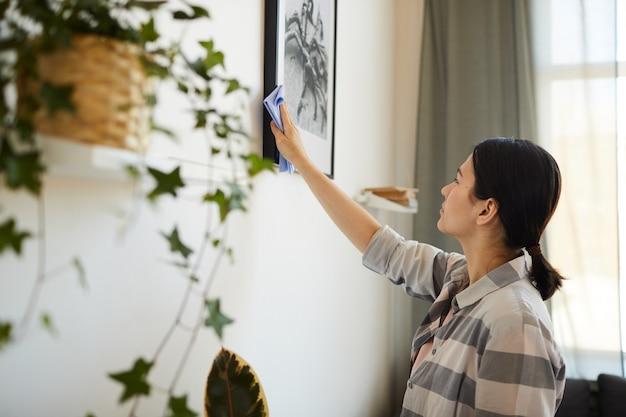 집에서 거실에서 집안일을하는 동안 사진에서 먼지를 닦는 젊은 여자