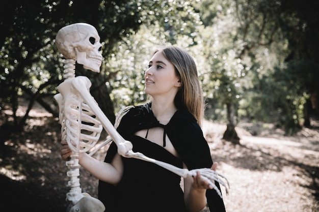 Young woman in witch clothes holding skeleton
