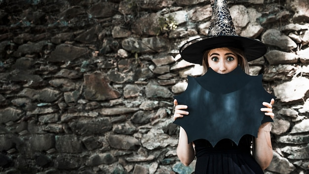 Young woman in witch hat closing mouth with halloween decoration