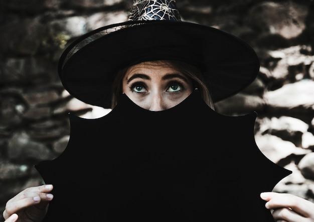 Giovane donna in cappello della strega che tiene decorazione di halloween vicino viso