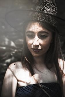 Giovane donna in cappello della strega che osserva da parte