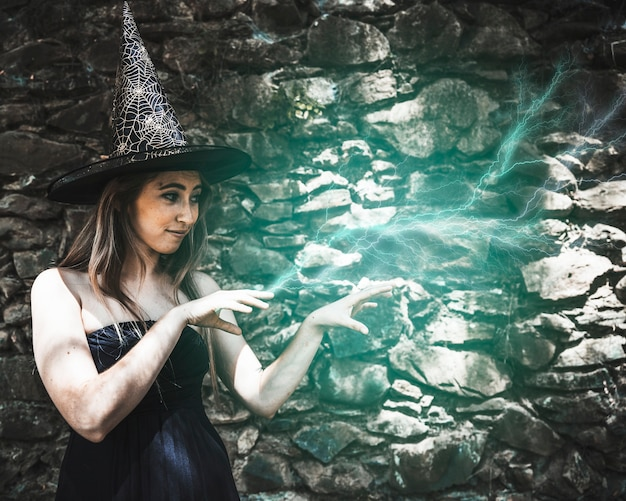 Young woman in witch hat pretending magic