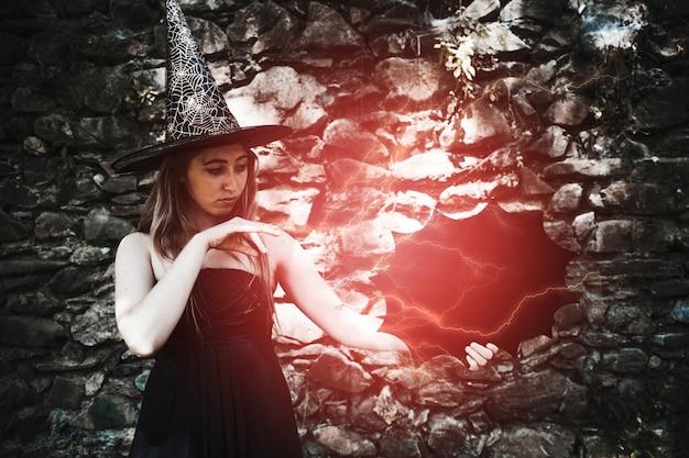 Giovane donna in cappello della strega che mostra magia con alleggerimento