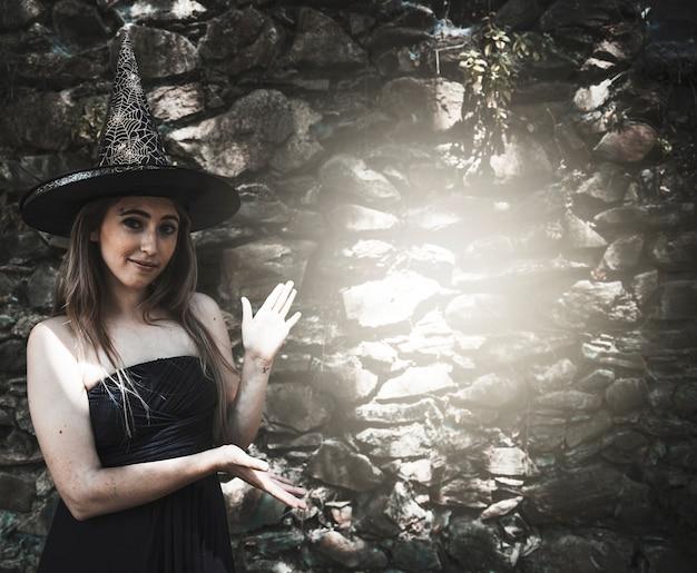Giovane donna in cappello della strega che sta vicino al punto luminoso sulla parete