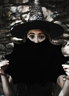 Young woman in witch hat with halloween decoration looking at camera