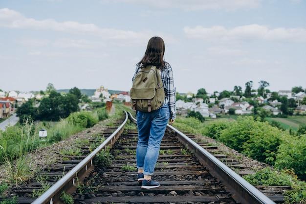 線路上のバックパックを持つ若い女性。