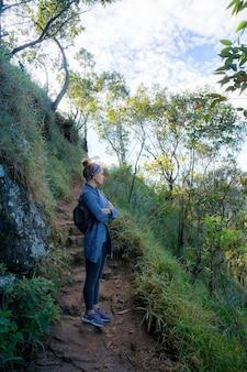 Молодая женщина с рюкзаком отдыхает, восхождение на гору