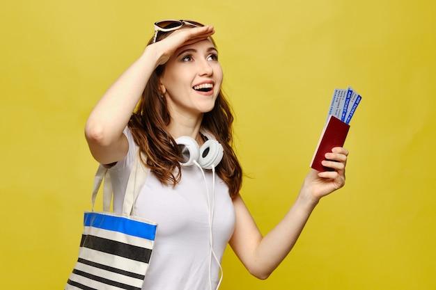 Молодая женщина с сумкой и билетами на самолет