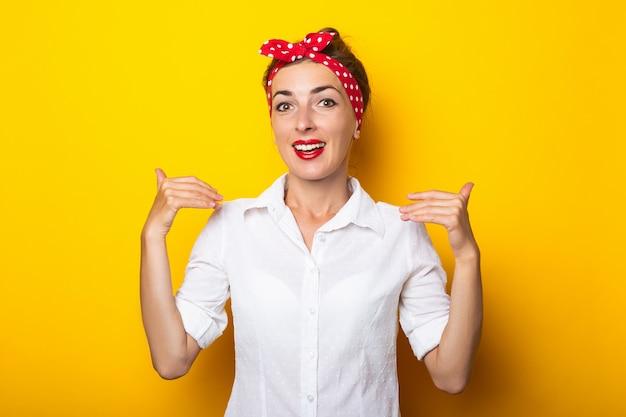 Молодая женщина с повязкой на голове делает жест «посмотри на меня» на желтой стене. баннер.