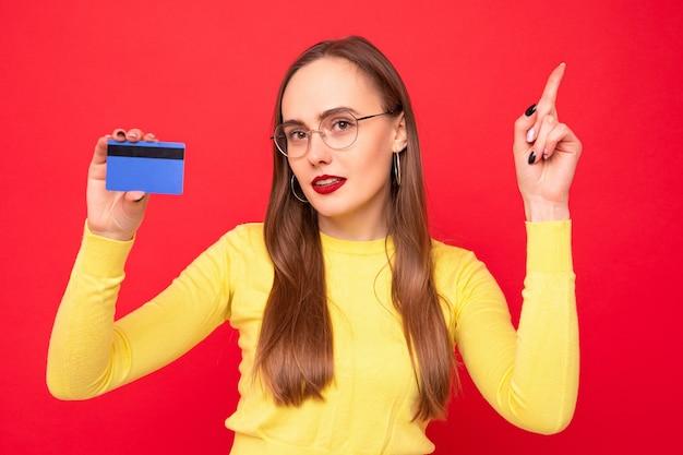 赤い背景の上の銀行カードを持つ若い女性