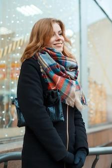 핸드백과 모직 패션 스카프가 달린 검은 장갑에 겨울 코트에 아름다운 미소를 지닌 젊은 여성이 축제 조명으로 장식 된 상점 창 근처의 거리에 서 있습니다. 즐거운 소녀