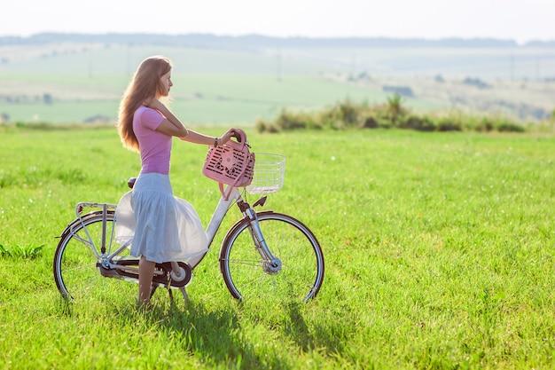 晴れた日に緑の野原に自転車を持つ若い女性