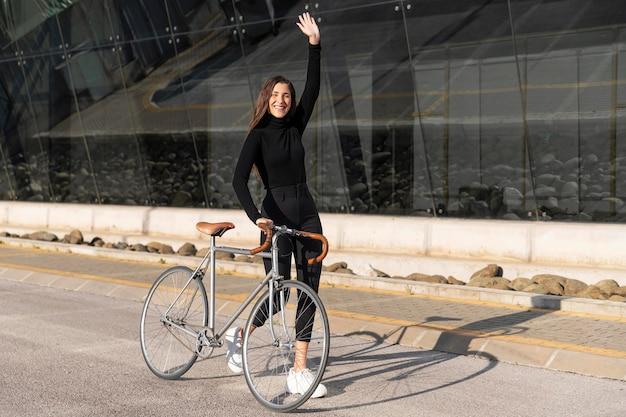 Молодая женщина с велосипедом на открытом воздухе