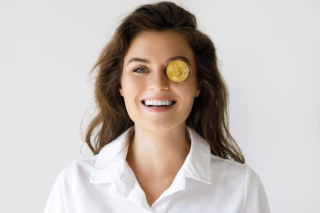 Молодая женщина с криптовалютой биткойн