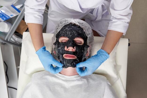 ビューティー サロンで顔に黒い酸素バブル マスクを持つ若い女性
