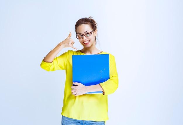 電話を求める青いフォルダーを持つ若い女性