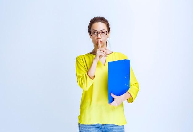 침묵을 요구하는 파란색 폴더를 가진 젊은 여성