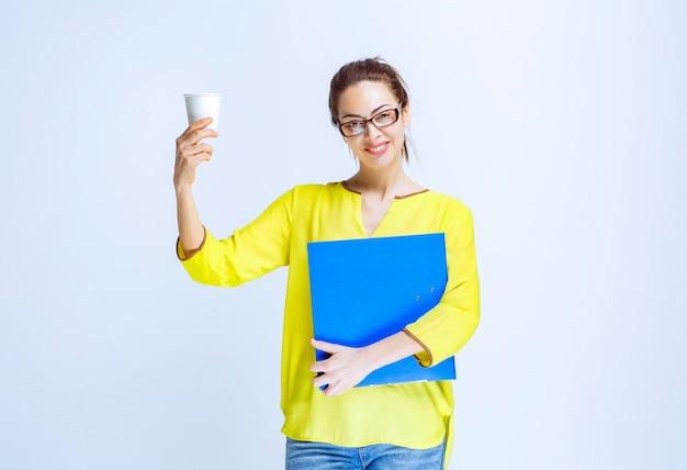Молодая женщина с синей папкой держит белый одноразовый стаканчик