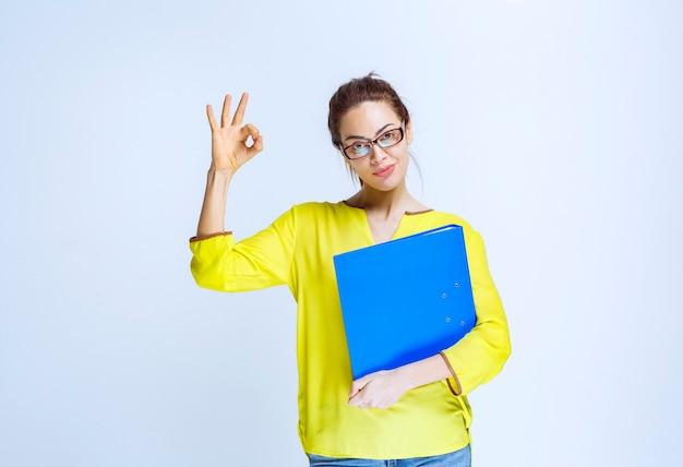 Молодая женщина с синей папкой, показывающей знак удовольствия
