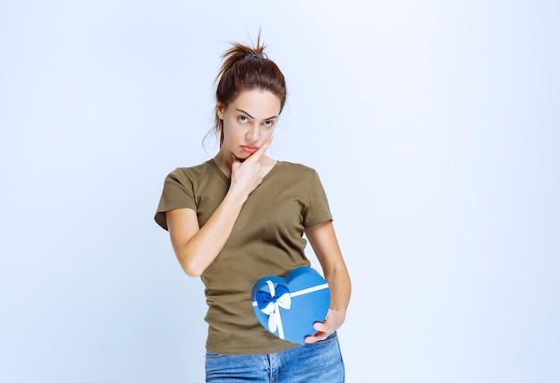 青いハート型のギフトボックスを持つ若い女性は不満に見えます