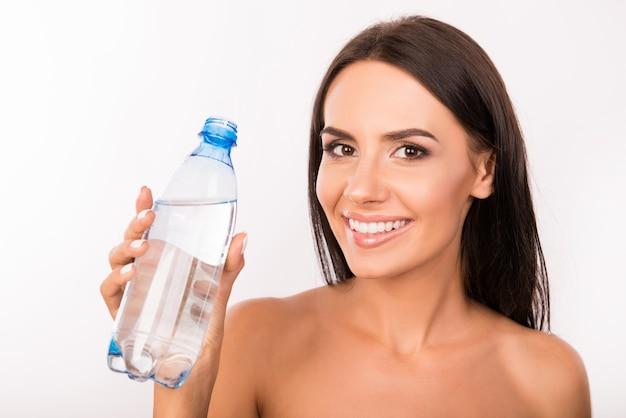 手にボトルを持つ若い女性