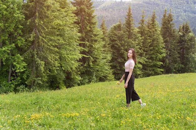 풀밭에 산책하는 꽃의 부케와 젊은 여자.