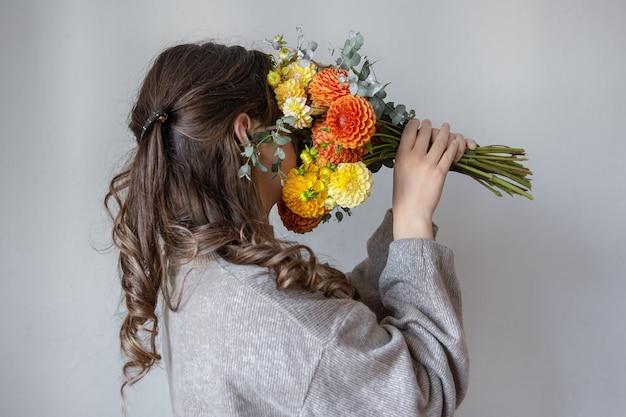 Молодая женщина с букетом свежих хризантем на сером фоне