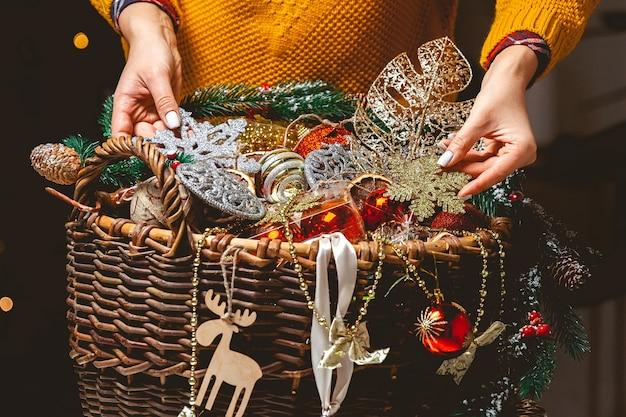 Молодая женщина с коробкой выбирает рождественские украшения в baske