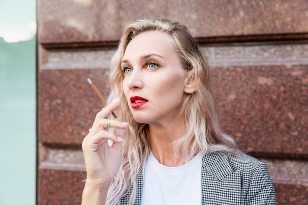 タバコを持つ若い女性。長い髪の美しいブロンドは、街で喫煙します。