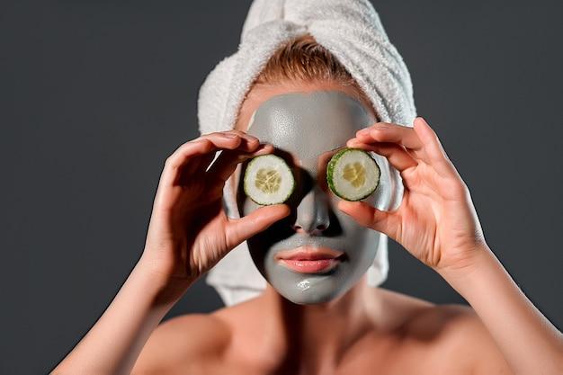 粘土のマスクを持つ若い女性。灰色の背景にきゅうりで目を覆っている魅力的な若い女性の写真。身だしなみ。