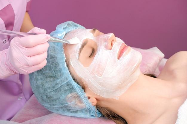 サロンで彼女の顔にクレンジングマスクを持つ若い女性。剥離手順