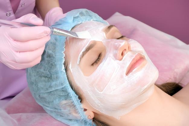 Молодая женщина с очищающей маской на лице в салоне. процедура пилинга