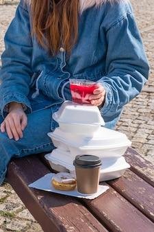 コートを着た若い女性がランチボックスと配達でコーヒーと食べ物を奪います。