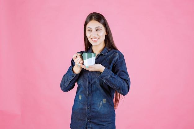 笑顔と前向きな気持ちのコーヒーカップを持つ若い女性