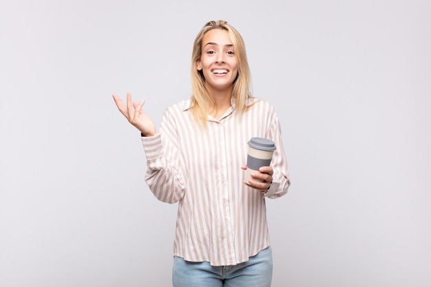커피가 행복하고 놀랍고 쾌활한 느낌, 긍정적 인 태도로 웃고 솔루션 또는 아이디어를 실현하는 젊은 여성