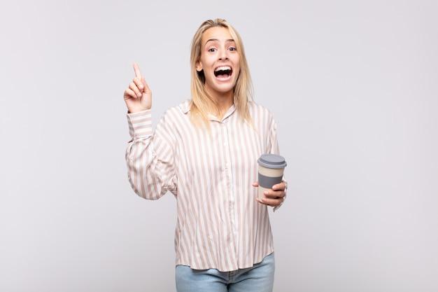 Молодая женщина с чашкой кофе чувствует себя счастливым и взволнованным гением, реализовав идею, весело подняв палец, эврика!