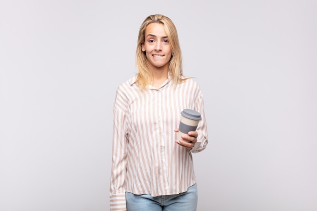 Молодая женщина с кофе выглядит озадаченной и сбитой с толку, нервно закусив губу, не зная ответа на проблему