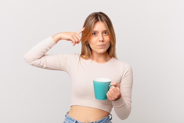 あなたが正気でないことを示して、混乱して困惑していると感じているコーヒーマグカップを持つ若い女性