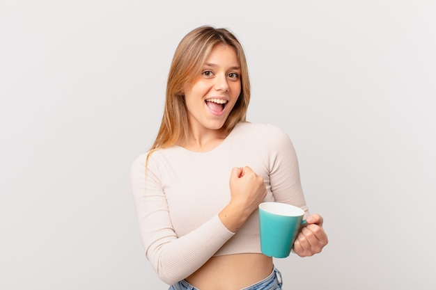 幸せを感じ、挑戦に直面している、または祝っているコーヒーマグカップを持つ若い女性