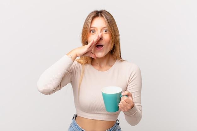 幸せを感じて、口の横に手で大きな叫びを与えるコーヒーマグカップを持つ若い女性
